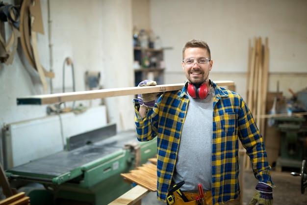 Professioneller lächelnder zimmermann mittleren alters, der holzplanke in der holzbearbeitungswerkstatt hält