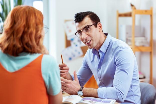 Professioneller lehrer. netter, freundlicher mann, der mit dem bleistift nach oben zeigt, während er seinem schüler neues material erklärt