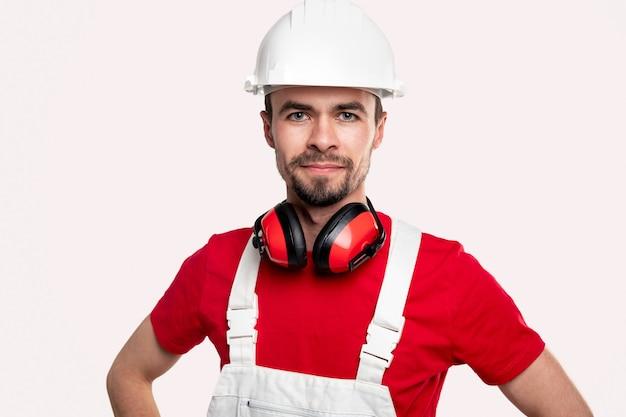 Professioneller männlicher arbeiter in arbeitskleidung und helm mit schützenden kopfhörern am hals