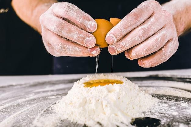 Professioneller männlicher bäcker, der teig mit eiern kocht