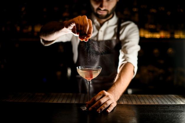 Professioneller männlicher barmixer, der ein cocktail im glas addiert einen zitronensaft dient