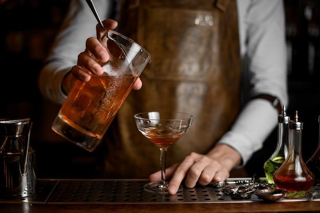 Professioneller männlicher barmixer, der ein köstliches braunes alkoholisches getränk vom messbecher zum cocktailglas gießt