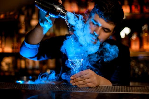 Professioneller männlicher barmixer, der einen rauch in das cocktailglas vom schüttel-apparat unter dem blaulicht gießt