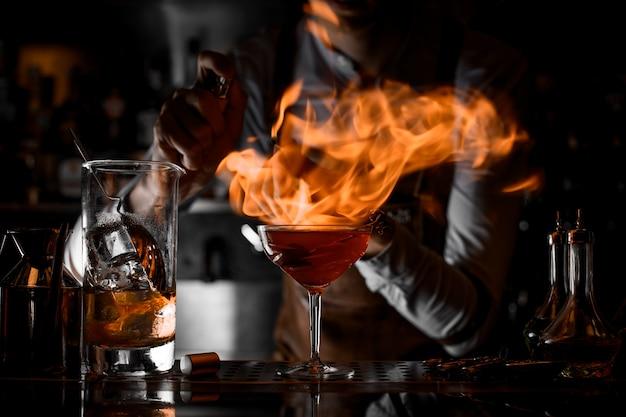Professioneller männlicher barmixer, der feuer vom feuerzeug auf das cocktailglas setzt