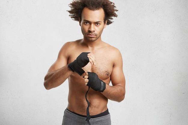 Professioneller männlicher boxer trägt schwarze schutzverbände an den händen und bereitet sich auf den kampf mit dem gegner vor