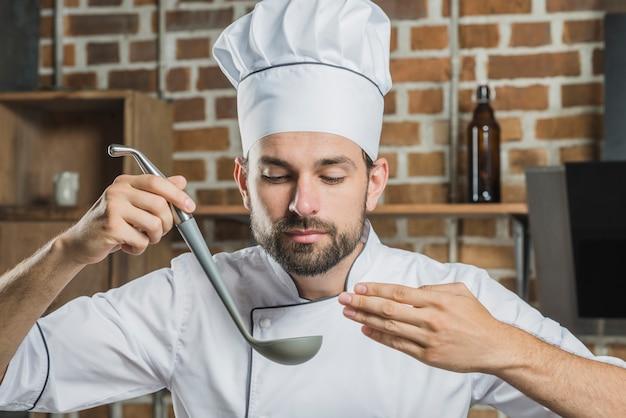 Professioneller männlicher chef, der die geschmackvolle suppe in der schöpfkelle riecht