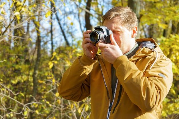 Professioneller männlicher fotograf, der draußen im gelben herbstwald schießt