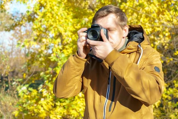 Professioneller männlicher fotograf, der draußen im gelben wald des herbstes auf moderner dslr-kamera schießt. leerer bereich mit kopierraum für text.