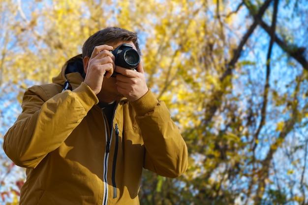 Professioneller männlicher fotograf, der draußen im gelben wald des herbstes auf moderner dslr-kamera schießt