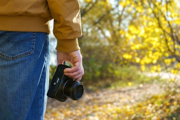 Professioneller männlicher fotograf hält schwarze moderne dslr-kamera in der hand mit natürlichem fall außerhalb des hintergrunds im sonnigen tag.