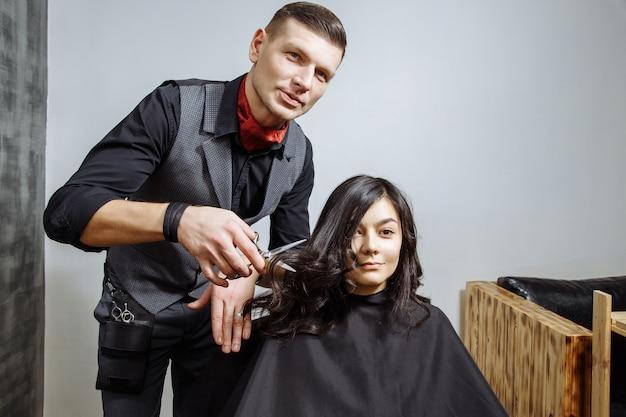 Professioneller männlicher friseurausschnitthaar zu einem weiblichen kunden