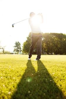 Professioneller männlicher golfspieler, der mit einem fahrer von einem abschlag schlägt