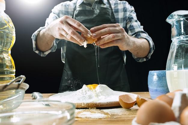 Professioneller männlicher koch besprüht teig mit mehl