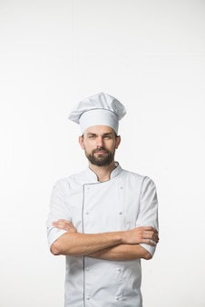 Professioneller männlicher koch in der weißen uniform des chefs, die gegen weißen hintergrund steht