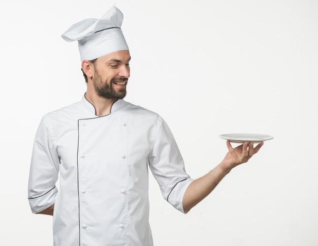 Professioneller männlicher koch in der weißen uniform des chefs, die teller auf weißem hintergrund darstellt