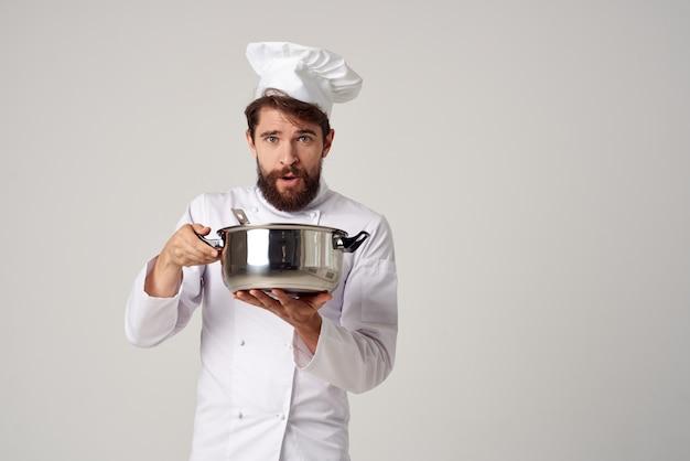Professioneller männlicher koch in einem restaurant mit einem kochtopf in den händen der erbringung von dienstleistungen