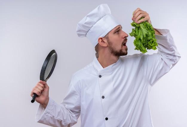 Professioneller männlicher koch kocht in der weißen uniform und im kochhut, der bratpfanne und frischen salat hält, der versucht, es zu riechen, das über weißem hintergrund steht
