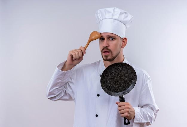 Professioneller männlicher koch kocht in der weißen uniform und im kochhut, der den kratzkopf der bratpfanne mit dem holzlöffel hält, der verwirrt steht, der über weißem hintergrund steht