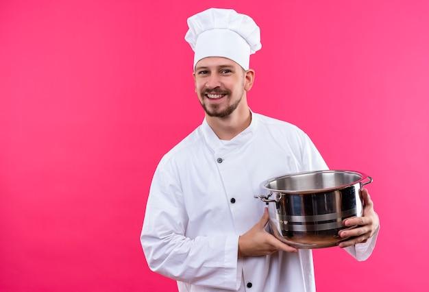Professioneller männlicher koch kocht in der weißen uniform und im kochhut, der eine leere pfanne hält, die fröhlich über rosa hintergrund stehend lächelt