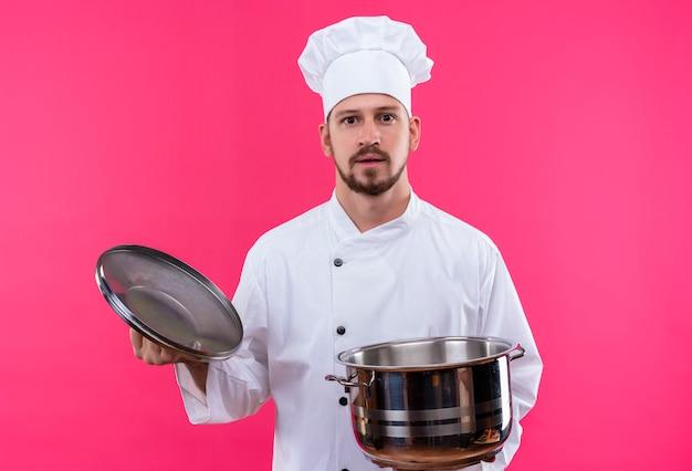 Professioneller männlicher koch kocht in der weißen uniform und im kochhut, der eine leere pfanne hält, die kamera mit ernstem sicherem ausdruck betrachtet, der über rosa hintergrund steht