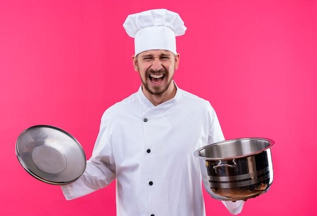 Professioneller männlicher koch kocht in der weißen uniform und im kochhut, der eine leere pfanne hält, die kamera schreit und mit aggressivem ausdruck schreit, der über rosa hintergrund steht