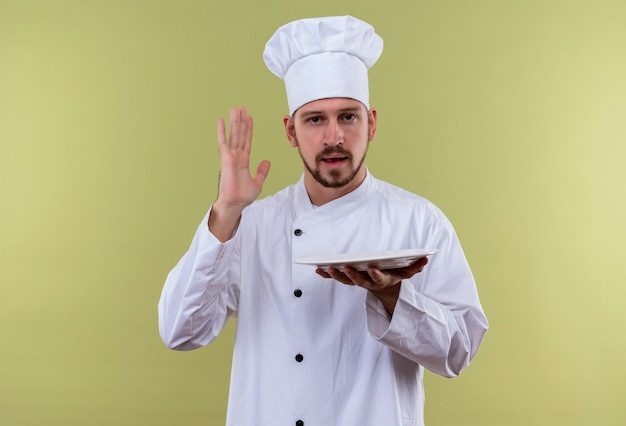 Professioneller männlicher koch kocht in der weißen uniform und im kochhut, der eine leere platte hält, die hand über grünem hintergrund anhebt