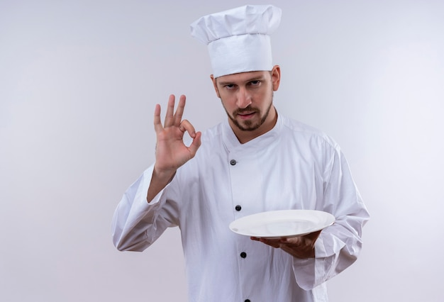 Professioneller männlicher koch kocht in der weißen uniform und im kochhut, der eine leere platte hält, die ok zeichen steht, das über weißem hintergrund steht