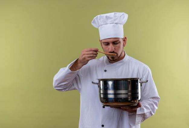 Professioneller männlicher koch kocht in der weißen uniform und im kochhut, der eine pfanne hält, die essen mit einer kelle schmeckt, die über grünem hintergrund steht
