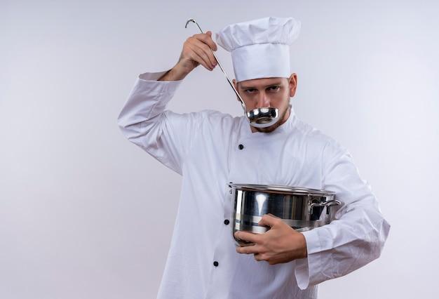 Professioneller männlicher koch kocht in der weißen uniform und im kochhut, der eine pfanne hält, die essen mit einer kelle schmeckt, die über weißem hintergrund steht