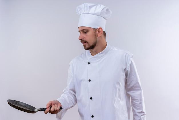 Professioneller männlicher koch kocht in der weißen uniform und im kochhut, der eine pfanne hält, die zuversichtlich steht, über weißem hintergrund zu stehen