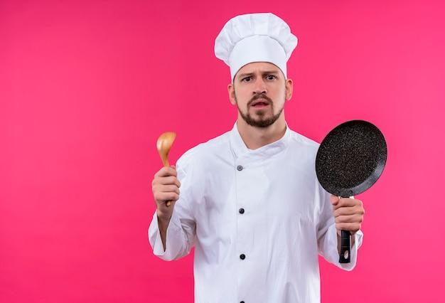 Professioneller männlicher koch kocht in der weißen uniform und im kochhut, der eine pfanne und einen holzlöffel hält, die kamera mit ernstem gesicht betrachten, das über rosa hintergrund steht