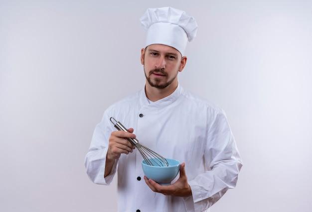 Professioneller männlicher koch kocht in der weißen uniform und im kochhut, der eine schüssel hält, die etwas mit schneebesen peitscht, der zuversichtlich steht, über weißem hintergrund zu stehen