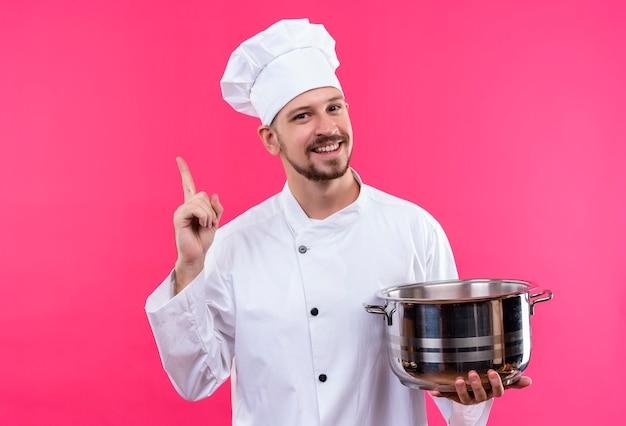 Professioneller männlicher koch kocht in der weißen uniform und im kochhut, der einen pfannenfinger hält, der fröhlich über rosa hintergrund stehend lächelt