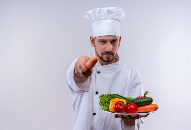 Professioneller männlicher koch kocht in der weißen uniform und im kochhut, der einen teller mit gemüse hält, das auf kamera mit karotte zeigt, die zuversichtlich steht, über weißem hintergrund zu stehen