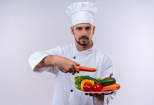 Professioneller männlicher koch kocht in der weißen uniform und im kochhut, der einen teller mit gemüse hält, der kamera mit ernstem sicherem ausdruck betrachtet, der über weißem hintergrund steht