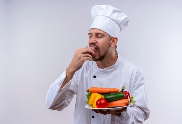 Professioneller männlicher koch kocht in der weißen uniform und im kochhut, der einen teller mit gemüse hält und frische tomate beißt, die über weißem hintergrund steht