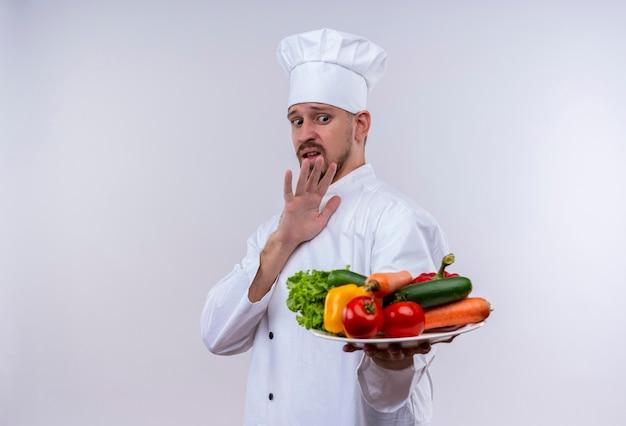 Professioneller männlicher koch kocht in der weißen uniform und im kochhut, der einen teller mit gemüse hält und verteidigungsgeste mit der hand macht, die über weißem hintergrund steht