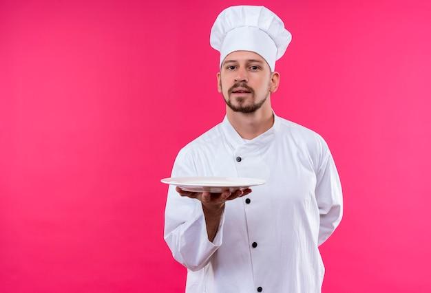 Professioneller männlicher koch kocht in der weißen uniform und im kochhut, der einen teller zeigt, der zuversichtlich steht, über rosa hintergrund zu stehen