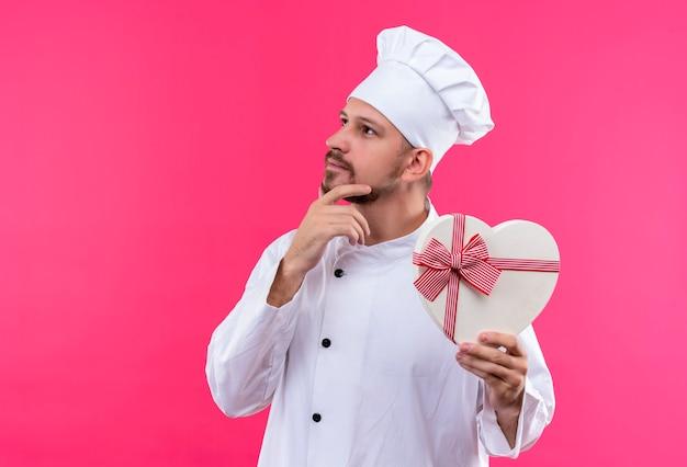 Professioneller männlicher koch kocht in der weißen uniform und im kochhut, der geschenkbox in einer herzform hält, die beiseite mit hand auf kinn mit nachdenklichem ausdruck auf gesicht steht, das über rosa hintergrund steht