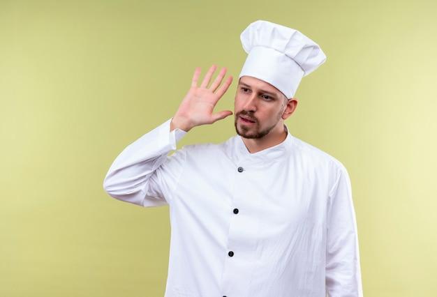 Professioneller männlicher koch kocht in der weißen uniform und im kochhut, der hand nahe seinem ohr hält, das versucht, das gespräch auf jemandem zu hören, der über grünem hintergrund steht