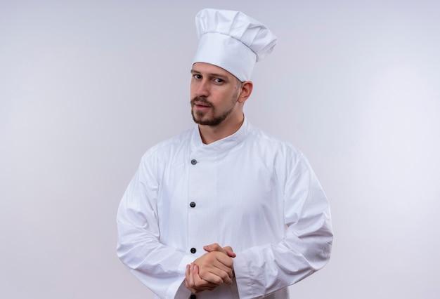 Professioneller männlicher koch kocht in der weißen uniform und im kochhut, der kamera mit vertraulichem ausdruck betrachtet, der hände reibt, die auf etwas warten, das über weißem hintergrund steht