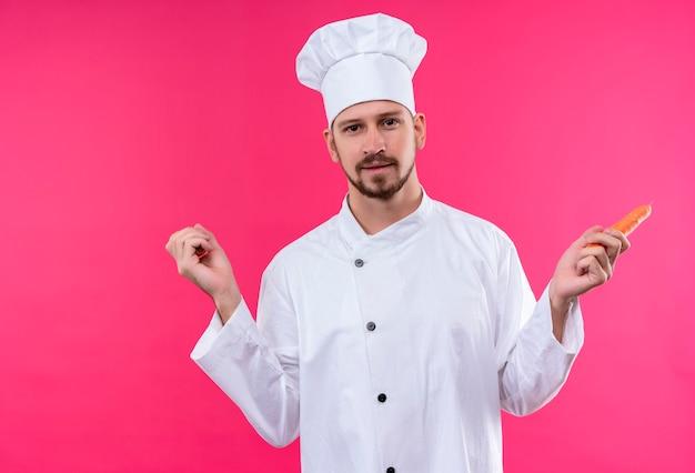 Professioneller männlicher koch kocht in der weißen uniform und im kochhut, der karotte hält, die kamera mit lächeln auf gesicht steht, das über rosa hintergrund steht