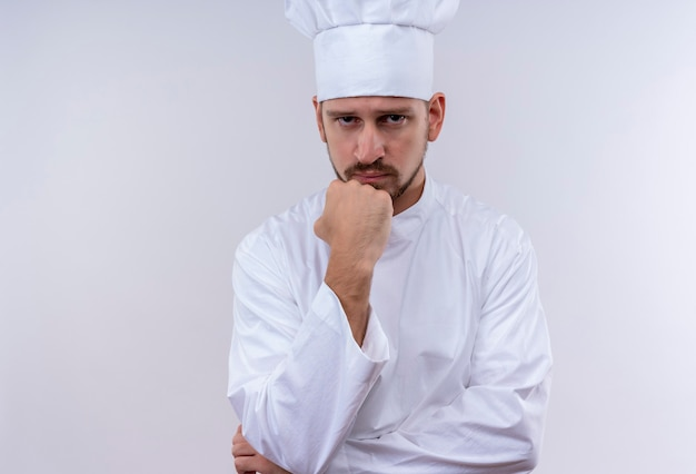 Professioneller männlicher koch kocht in der weißen uniform und im kochhut, der mit faust auf kinn mit nachdenklichem ausdruck auf gesicht über weißem hintergrund steht