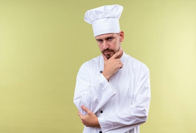 Professioneller männlicher koch kocht in der weißen uniform und im kochhut, der mit hand auf kinn mit nachdenklichem ausdruck steht und kamera betrachtet, die über grünem hintergrund die stirn runzelt