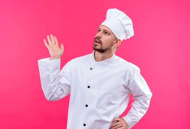 Professioneller männlicher koch kocht in der weißen uniform und im kochhut, der mit verwirrendem ausdruck über rosa hintergrund nach oben schaut