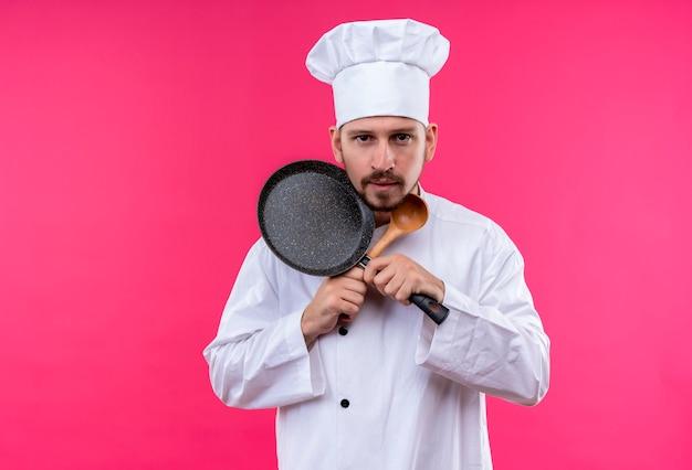 Professioneller männlicher koch kocht in der weißen uniform und im kochhut, der pfanne und hölzernen löffel kreuzenden hände hält, die kamera betrachten, die über rosa hintergrund steht