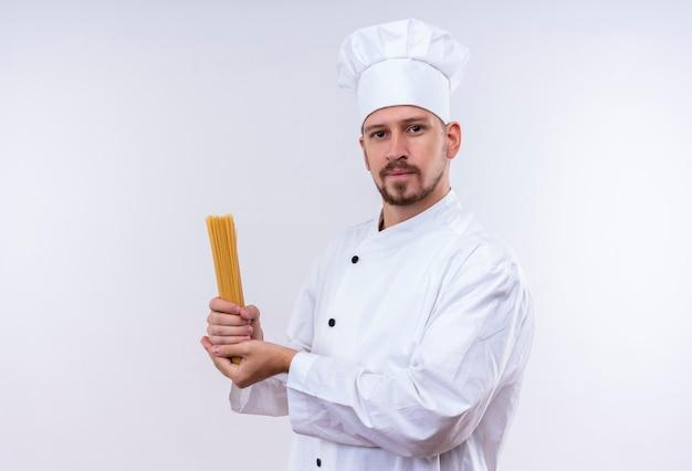 Professioneller männlicher koch kocht in der weißen uniform und im kochhut, der rohe spaghetti-nudeln hält, die zuversichtlich stehen, über weißem hintergrund zu stehen