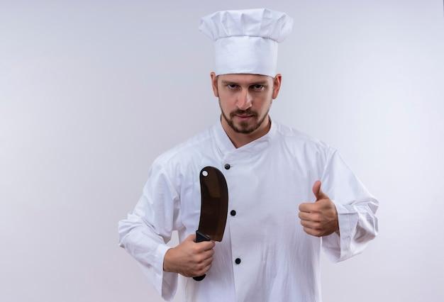 Professioneller männlicher koch kocht in der weißen uniform und im kochhut, der scharfes messer hält, das daumen oben zeigt, das sicher steht, über weißem hintergrund zu stehen