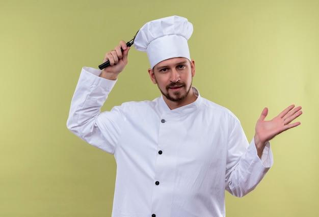 Professioneller männlicher koch kocht in der weißen uniform und im kochhut, der schneebesen hält, der hand schaut, die verwirrt und unsicher steht über grünem hintergrund steht