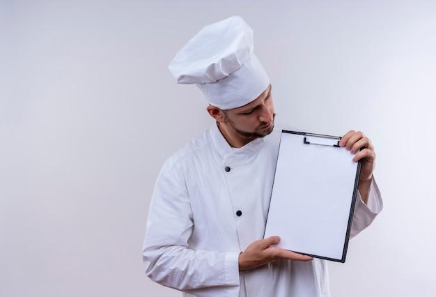 Professioneller männlicher koch kocht in der weißen uniform und im kochhut, der zwischenablage mit leeren seiten demonstriert, die über weißem hintergrund stehen